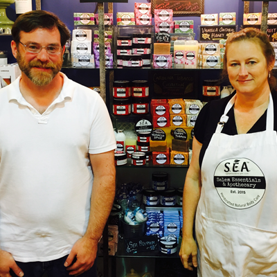 Candace and Jonathan from Salem Essentials & Apothecary stand in front of their display in Artisans in Greenville, North Carolina.